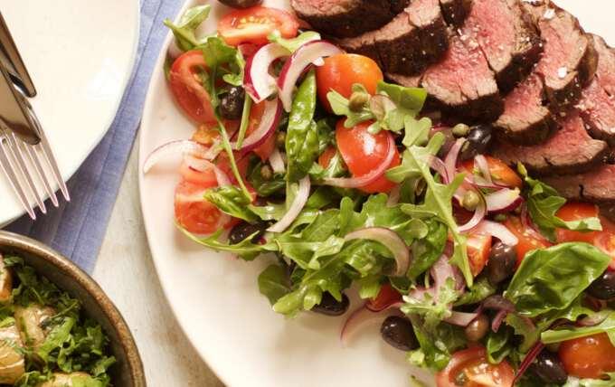 мясо и салат на праздничном блюде к новому году петуха